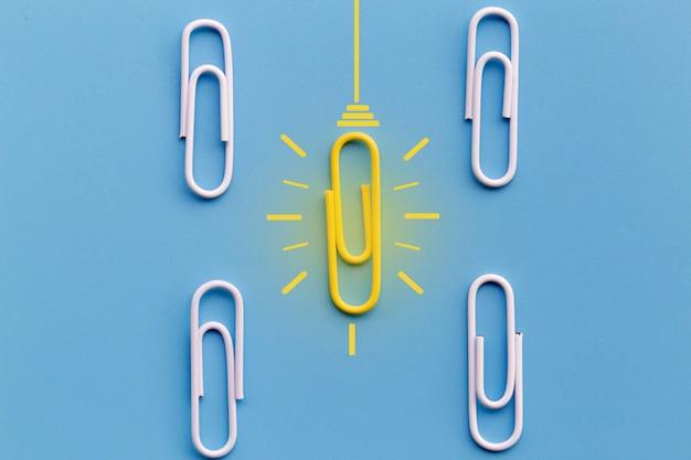 Konzept der großartigen ideen mit der papierklammer, denkend, kreativität, glühlampe auf blauem hintergrund, neues ideenkonzept.