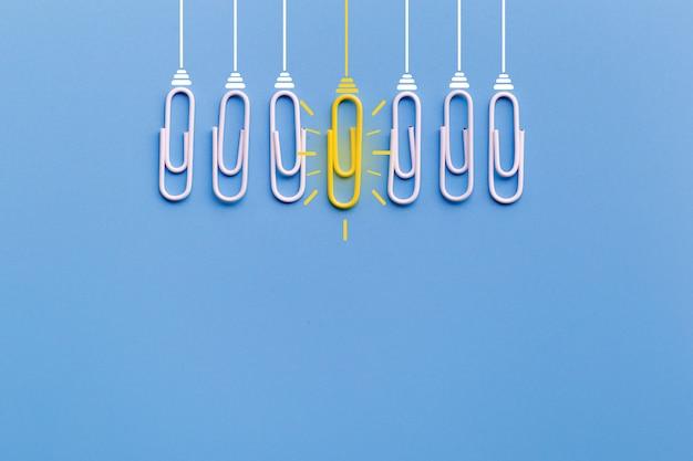 Konzept der großartigen ideen mit der papierklammer, denkend, kreativität, glühlampe auf blauem hintergrund.