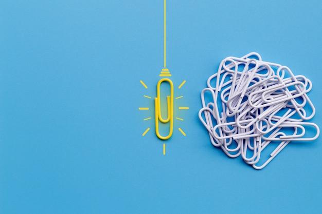 Konzept der großartigen ideen mit glühlampe der denkenden kreativität der papierklammer auf blauem hintergrund