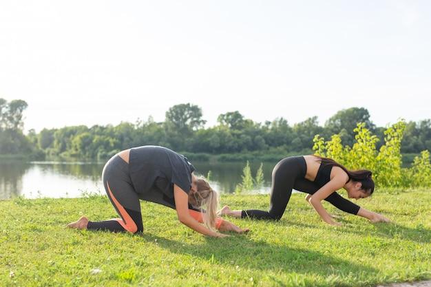 Konzept der harmonie und des gesunden lebensstils - junge schlanke frauen in sportbekleidung, die yoga im freien praktizieren.