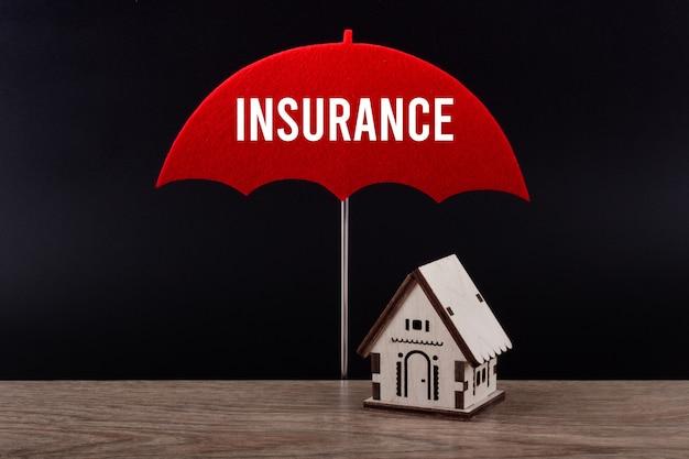 Konzept der hausversicherung. holzhaus unter rotem regenschirm mit textversicherung.