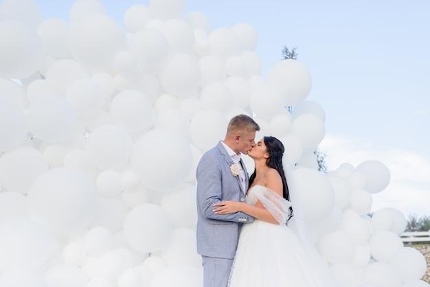 Konzept der hochzeitszeremonie schöne brünette braut umarmt und küsst ihren bräutigam auf einem hintergrund von weißen ballons