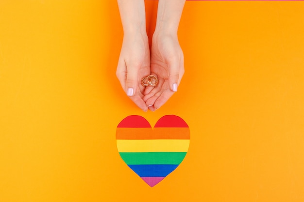 Konzept der homosexuellen ehe mit regenbogenflagge und -ringen