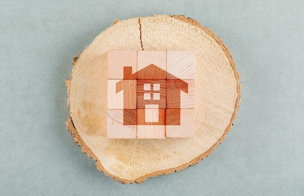 Konzept der immobilie mit holzklötzen, hölzerne menschliche figur draufsicht.