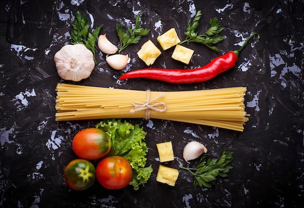 Konzept der italienischen küche. pasta, tomaten, olivenöl, pfeffer, petersilie und käse. selektiver fokus oben