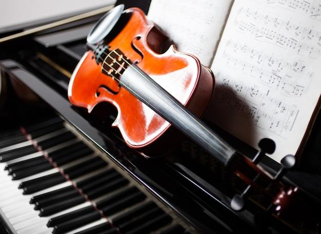 Konzept der klassischen musik: violine und partitur auf einem klavier