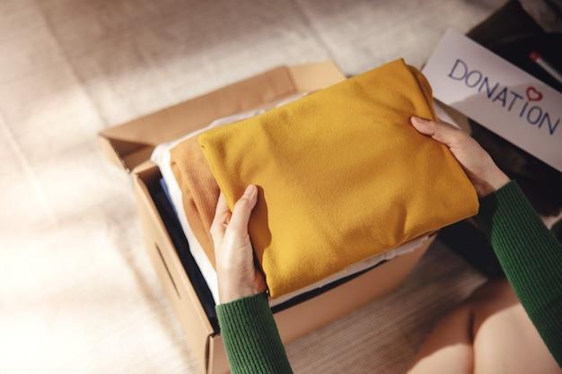 Konzept der kleiderspende. stoffbox mit spendenetikett. frau, die zu hause gebrauchtes altes kleidungsstück vorbereitet. ansicht von oben