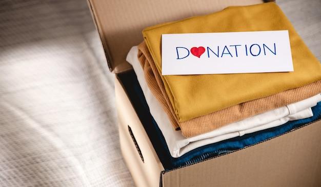 Konzept der kleiderspende. stoffbox mit spendenetikett. vorbereitung gebrauchter alter kleidungsstücke zu hause. ansicht von oben