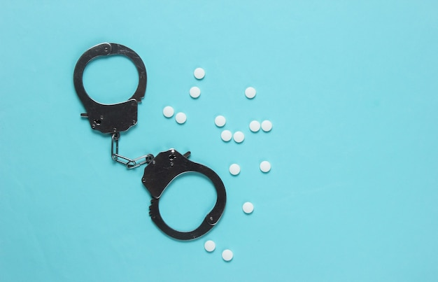 Konzept der korruption in der medizin. pillen und handschellen auf blauem hintergrund. medizinisches stillleben. strafe für verbrechen.
