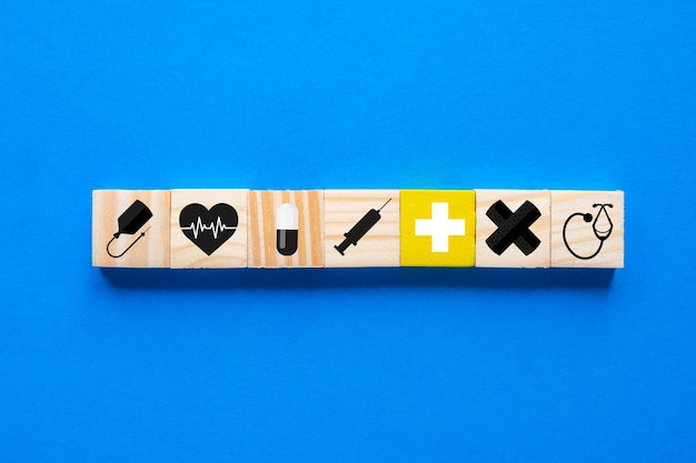 Konzept der krankenversicherung, medizinisches symbol in holzklötzen, blauer hintergrund, kopierraum