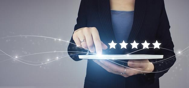 Konzept der kundenerfahrung, beste exzellente dienstleistungen. weiße tablette in der hand der geschäftsfrau mit digitalem hologramm fünf sterne 5 bewertungszeichen auf grau. hand des berührens steigt auf fünf sterne an.