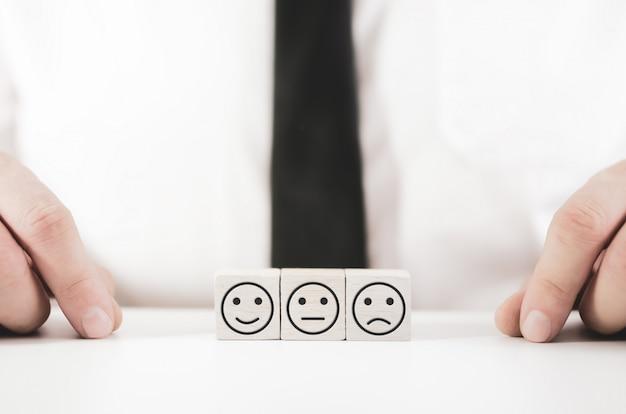 Konzept der kundenzufriedenheit mit drei weißen holzklötzen mit unterschiedlichen ausdrucksformen der zufriedenheit mit dem geschäftsmann im raum
