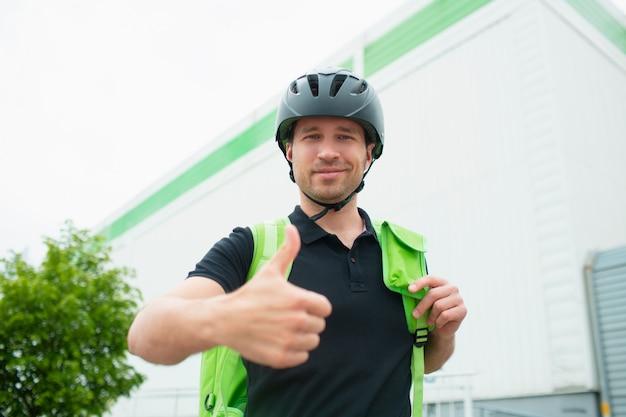 Konzept der lebensmittellieferung. der essenslieferant nutzt ein smartphone, um kunden schneller zu erreichen. kurier hat einen kühlschrank in einem grünen rucksack. er schaut in die kamera und hält seinen daumen hoch.
