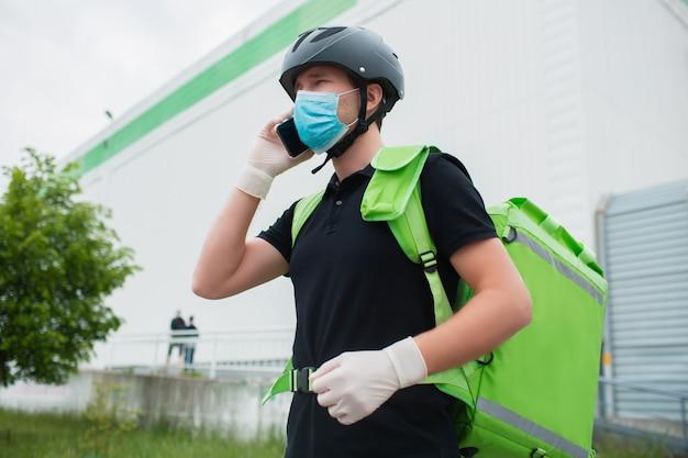 Konzept der lebensmittellieferung. der essenslieferant nutzt ein smartphone, um kunden schneller zu erreichen. kurier hat einen kühlschrank in einem grünen rucksack. er trägt eine medizinische maske und handschuhe