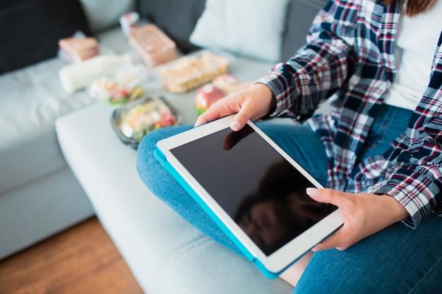 Konzept der lebensmittellieferung. eine junge frau bestellt zu hause essen mit einer tablette.