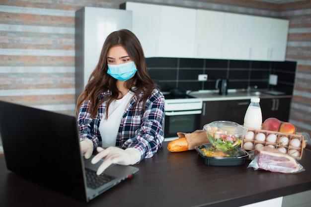 Konzept der lebensmittellieferung. eine junge frau in einer medizinischen maske und einem gummi-einwegmaskenhandschuh bestellt essen mit einem laptop zu hause. auf dem tisch stehen milch, salate in kisten, fleisch, essen, obst, eier, brot