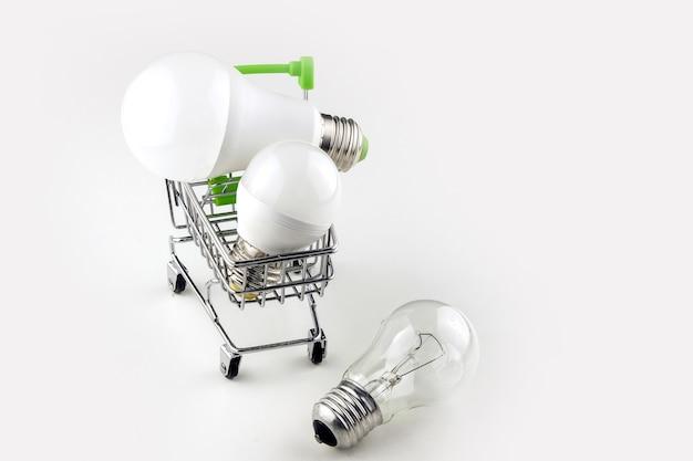 Konzept der modernen wirtschaftlichen beleuchtung. energiesparlampen werden in einen korb auf rädern gelegt. einfache glühbirne liegt auf dem tisch.