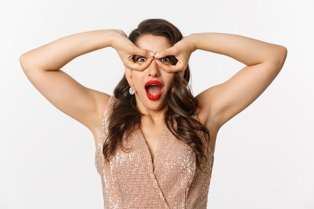 Konzept der neujahrsfeier und winterferien. nahaufnahme einer erstaunten und aufgeregten frau in luxuskleid, rotem lippenstift, blick durch die handbrille, weißer hintergrund