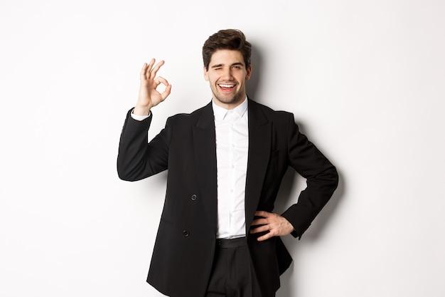 Konzept der neujahrsparty, feier und lifestyle. porträt eines selbstbewussten, erfolgreichen geschäftsmannes im anzug, der ein gutes zeichen zeigt und zwinkert, etwas gutes, weißer hintergrund genehmigen.