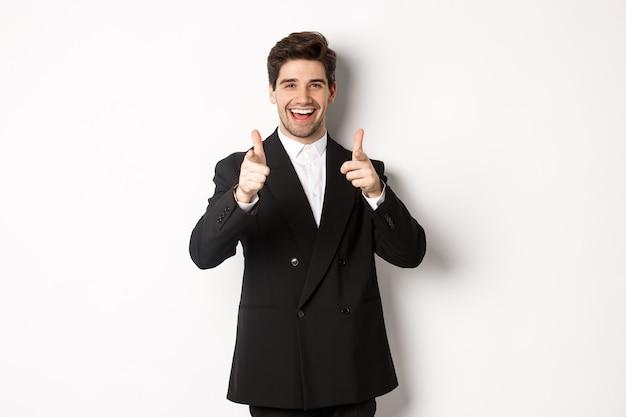 Konzept der neujahrsparty, feier und lifestyle. schöner und erfolgreicher kerl im schwarzen anzug, der mit den fingern auf die kamera zeigt und ihnen gratuliert und auf weißem hintergrund steht.