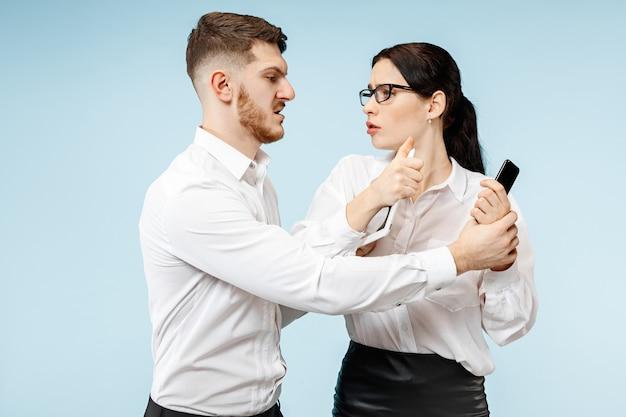 Konzept der partnerschaft im geschäft. junger emotionaler mann und frau gegen blauen hintergrund im studio. menschliche emotionen und partnerschaftskonzept