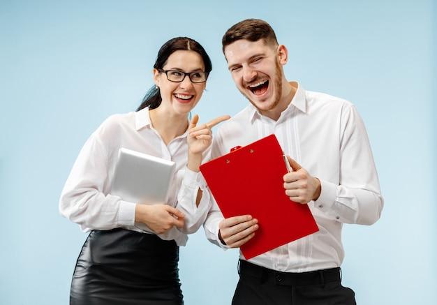 Konzept der partnerschaft im geschäft. junger glücklicher lächelnder mann und frau, die gegen blauen hintergrund im studio stehen