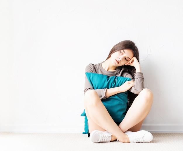 Konzept der psychischen gesundheit. schöne traurige frau im braunen hemd und in den schwarzen ledershorts, die auf dem boden mit kissen tief in gedanken sitzen