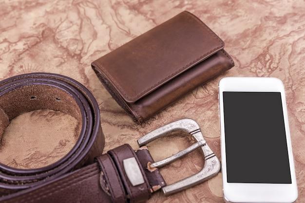 Konzept der reise auf der ganzen welt mit brieftasche, handy, gürtel auf der weltkarte