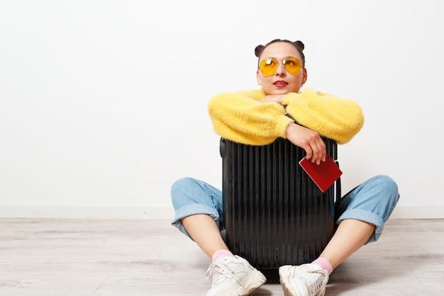 Konzept der reise. glückliches frauenmädchen mit koffer und pass.
