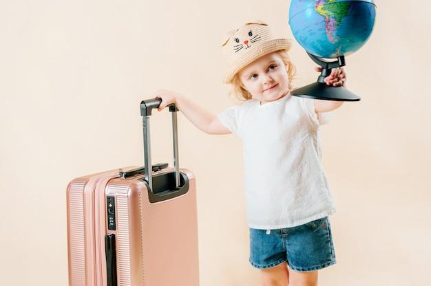 Konzept der reise, tourismus. mädchen auf einem isolierten hält eine kugel, ein koffer steht in der nähe