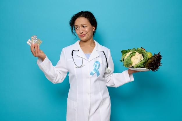 Konzept der richtigen ernährung und gesundheitsversorgung. selbstbewusste ärztin in medizinischem kittel mit blauem diabetes-bewusstseinsband hält einen teller mit gesundem veganem essen und blister mit medikamenten in ihren händen.