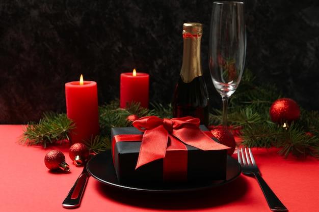 Konzept der romantischen neujahrstabelle mit geschenkbox auf rotem tisch