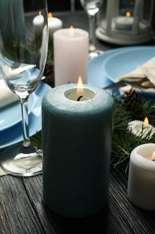 Konzept der romantischen neujahrstabelle mit kerzen auf holztisch
