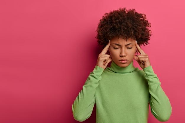 Konzept der schlechten gefühle. ernsthafte schwarze frau mit afro-locken hält zeigefinger an den schläfen, leidet unter kopfschmerzen