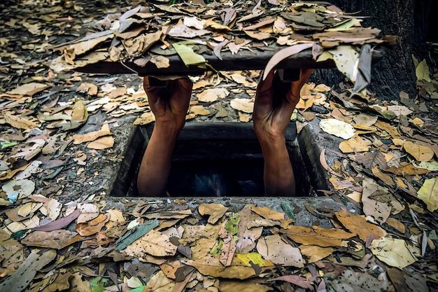 Konzept der selbstisolation von viren und krankheiten. hopper aus gehorsam. mann versteckt sich in einem loch. vietnams cu-chi-tunnel zur tarnung während des us-vietnamkriegs. luftschutzbunker vor der bombardierung. verstecken in