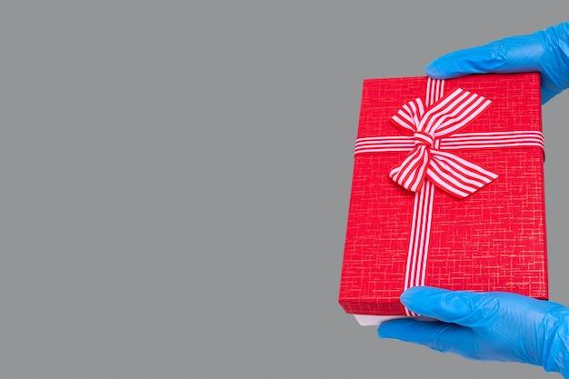 Konzept der sicheren lieferung von geschenken. hände in blauen handschuhen halten eine rote geschenkbox mit einer schleife auf dem trendigen ultimate grey-hintergrund. sichere geschenke während der coronavirus-pandemie 2021