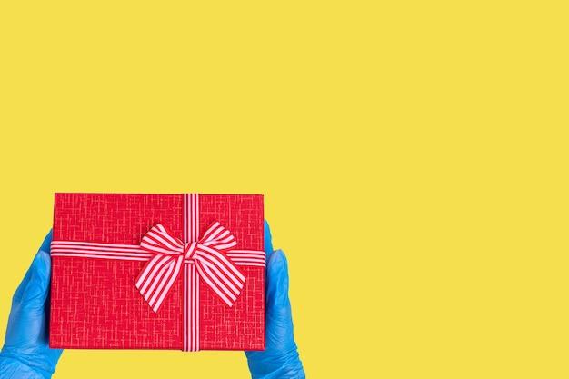 Konzept der sicheren lieferung von geschenken. hände in blauen handschuhen halten eine rote geschenkbox mit einer schleife