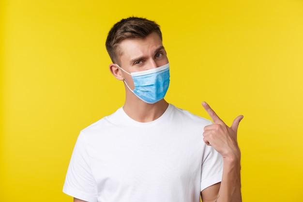 Konzept der sozialen distanzierung, covid-19 und emotionen der menschen. schöner entschlossener junger mann, der mit dem finger auf die medizinische maske im gesicht zeigt, wie empfohlen, draußen zu essen, gelber hintergrund.