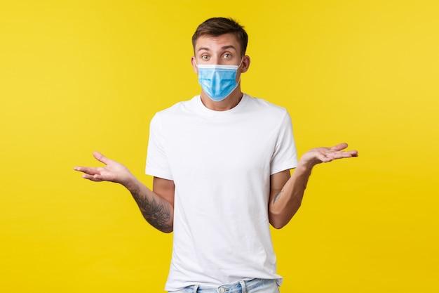 Konzept der sozialen distanzierung, covid-19 und emotionen der menschen. verwirrter und ahnungsloser gutaussehender mann in medizinischer maske und einfachem t-shirt, ahnungslos die achseln zuckend, keine ahnung, verwirrt zu antworten, gelber hintergrund