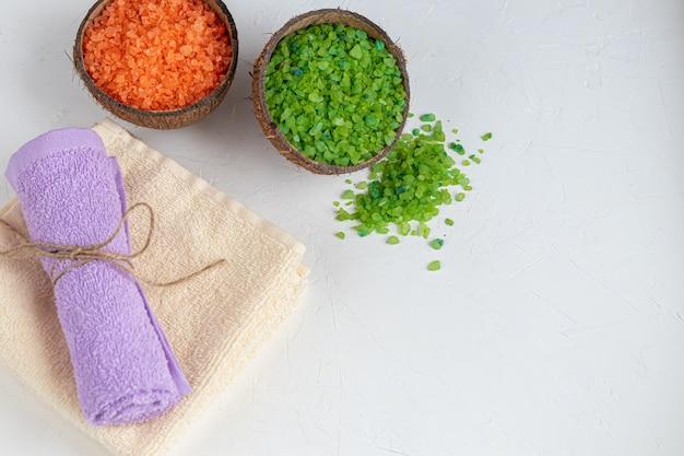 Konzept der spa-behandlung mit natürlich duftendem zweifarbigem meeresbadesalz in kokosnusshälften und badetüchern. umweltfreundliches produkt.