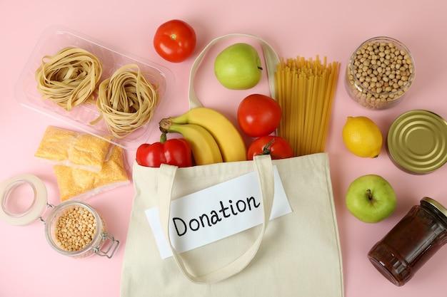 Konzept der spende mit essen auf rosa hintergrund