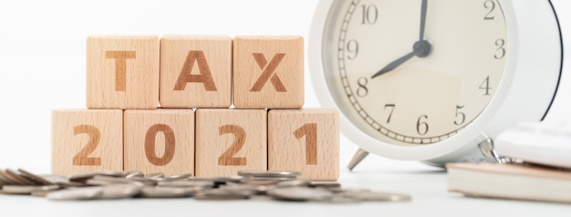 Konzept der steuersaison, die sich mit holzklötzen, münzen und wecker über weißem hintergrund nähert.