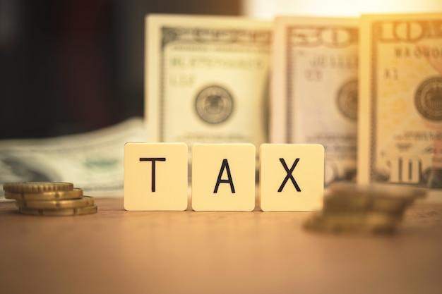Konzept der steuersenkung, vermeidung. kosten und auslagen des unternehmens, besteuerung. bezahlen sie den schuldenhintergrund mit desktop- und us-dollar-scheinen