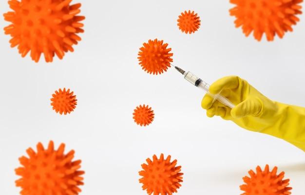 Konzept der suche und prüfung eines impfstoffs eine hand in einem gelben schutzhandschuh führt eine injektion in ein modell einer zelle ein