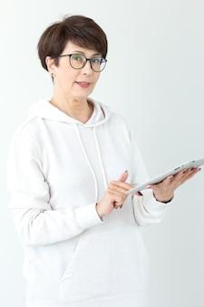Konzept der technologien und der modernen leute - schöne frau 50 jahre alt mit tablette mit kurzen haaren