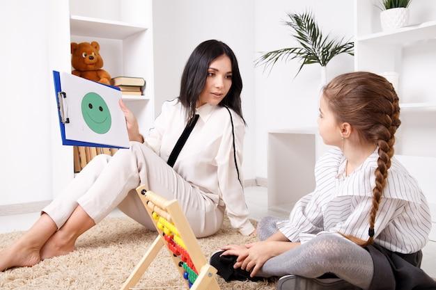 Konzept der therapeutensitzung. psychologin, die mit süßem kleinen kind arbeitet.