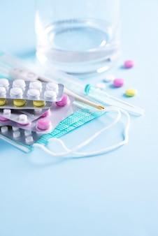 Konzept der therapie, prävention der virusgrippe, virusangriff, erkältungspillen, antibiotika und vitamine, schützende medizinische gesichtsmasken über blauem hintergrund. coronavirus (covid-19. speicherplatz kopieren