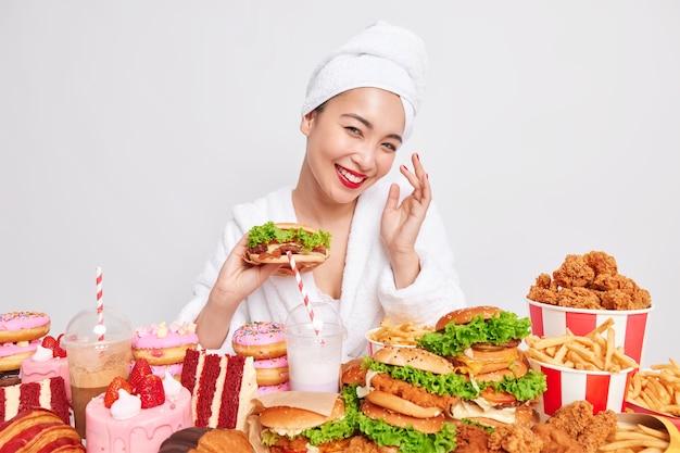 Konzept der ungesunden ernährung. positive junge asiatin mit gesunder haut lächelt breit hält hamburger isst fast food