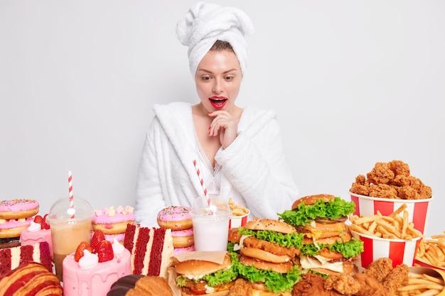 Konzept der ungesunden ernährung. überraschte frau hat rote lippen, die sehr hungrig sind, und schaut auf den tisch, der mit junk-food überladen ist