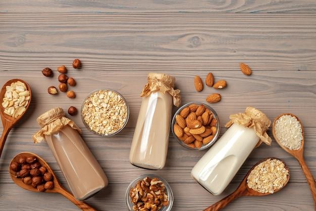 Konzept der veganen bio-milch ohne milchprodukte mit glasmilchflasche und massenprodukten auf hölzernem hintergrund